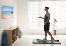Sporty man with remote control training on walking treadmill and watching TV at home