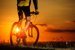 Sporty Man Riding a Bicycle on the Country Road. Royalty Free Stock Photos