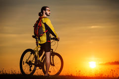 Sporty Man Riding a Bicycle on the Country Road. Royalty Free Stock Image