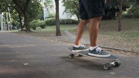A sporty man is riding a skateboard in the park in the summer stock video