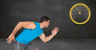 Sporty man running while looking at clock on wall. Digital composite of Sporty man running while looking at clock on wall Royalty Free Stock Images