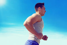Sporty man running outdoors on a against blue sky Royalty Free Stock Photo