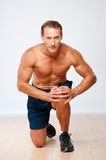 Sporty man in shorts on his knee Royalty Free Stock Photos