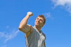 Sporty man showing his strength. Sporty young man showing his strength. Outdoor training Stock Image