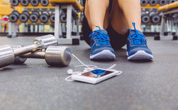 Sporty man sitting with dumbbells and smartphone Stock Image