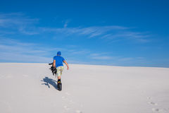 Sporty man with a snowboard goes up the sand dune Stock Photos