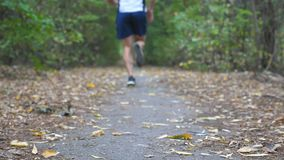 Sporty man sprinting fast along trail at early autumn forest. Strong sportsman running along path at nature. Athletic. Guy exercising outdoor. Concept of stock footage