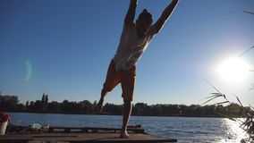 Sporty man standing at yoga pose on wooden jetty at lake. Young guy doing exercise at nature. Athlete balancing on one. Leg outdoor. Beautiful landscape stock video