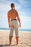 Sporty man stands on sandy summer beach Royalty Free Stock Photos