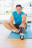 Sporty man stretching hand to leg in fitness studio Stock Photos