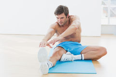 Sporty man stretching hands to leg in fitness studio Royalty Free Stock Image
