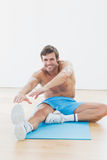 Sporty man stretching hands to leg in fitness studio Stock Photo