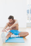 Sporty man stretching hands to leg in fitness studio Stock Image