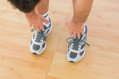 sporty man stretching hands to legs in fitness studio Royalty Free Stock Photos