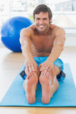 Sporty man stretching hands to legs in fitness studio Stock Photography