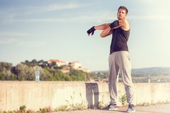 Stretching arms. Sporty man stretching on summer day Royalty Free Stock Photography