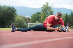 Young Man Is Streching Outdoors. Sporty Man Stretching and Warming Up Legs for Running Fitness Workout on Track Exercising Outside Stock Photos