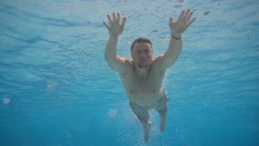 Sporty man swimming under the water. Young active swimmer diving in the pool. Man swimming underwater. Active lifestyle concept stock video footage