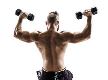 Sporty man in training pumping up muscles of the back and hands with dumbbells. Stock Image