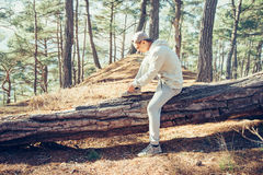 Sporty man tying shoelaces in the forest. Sporty young man sitting on fallen tree trunk and tying shoelaces outdoor in the pine forest Stock Image
