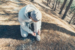 Sporty man tying shoelaces. Sporty young man tying shoelaces in the forest outdoor Stock Images