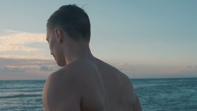 Sporty man on vacation going to the beach at sunrise. Slow motion video. Sporty man on vacation going to the beach at sunrise. Slow motion video stock video footage