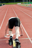 Sporty man waiting in starting block. In a stadium Stock Image