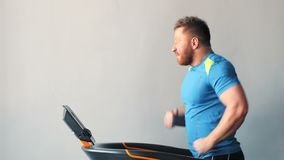 Sporty man walking on treadmill at the gym.  stock video