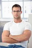 Sporty man wearing glasses sitting arms crossed stock images