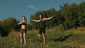 Sporty man and woman doing triangle pose in the park at sunset stock footage