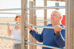 Sporty mature couple training with chin-up bar Stock Photography