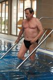 Sporty mature man going swimming stock images