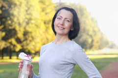 Sporty mature woman hold bottle with water outdoor on sunny day in the park. Healthy lifestyle Royalty Free Stock Photography