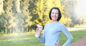 Sporty mature woman hold bottle with water outdoor on sunny day in the park. Healthy lifestyle concept royalty free stock image