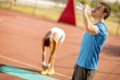 Sporty man drinking water while young woman doing exercise in th stock images