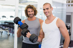 Sporty men exercising with dumbbells in gym Stock Photography