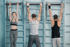 Sporty men and woman hanging on sport equipment. Sporty men and women hanging on sport equipment in gym Stock Images