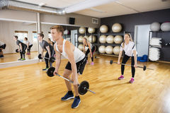 Sporty Men And Women Lifting Barbells In Gym Stock Photo