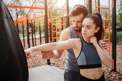 Sporty man and woman are standing in the park and exercising together. Girl is trying to boxing while her trainer is royalty free stock image