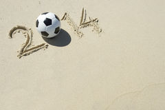 Sporty 2014 Message in Sand with Football Soccer Ball Royalty Free Stock Photography