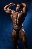 Sporty mięśniowy mężczyzna bodybuilder pokazuje jego siłę na a i ciało Obraz Royalty Free