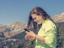 Sporty millenial отправляющ СМС ее пешие достижения стоковая фотография