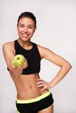 Sporty mixed race woman showing an apple to camera Stock Photography