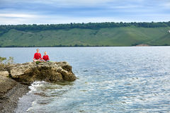 Sporty mother and daughter doing yoga on the rock near beautiful river. Beautiful mother and daughter dressed in the sportwear and barefoot. Horizontal photo Stock Images