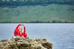 Sporty mother and daughter doing yoga on the rock near beautiful river. Royalty Free Stock Photos