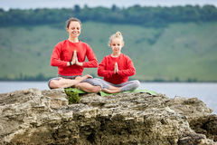 Sporty mother and daughter doing yoga on the rock near beautiful river. Royalty Free Stock Image