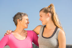 Sporty mother and daughter smiling at each other royalty free stock image