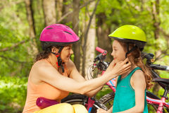 Sporty mother helping her daughter to clasp helmet Royalty Free Stock Photography
