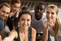 Sporty multiracial friends taking group selfie holding looking a Stock Photography