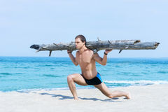 Sporty and muscled man training on a summer beach Stock Image